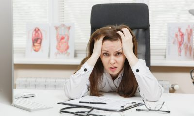 Young tired exhausted woman sitting at desk, working on computer with medical documents in light office in hospital. Female doctor in medical gown sleep in consulting room Healthcare medicine concept